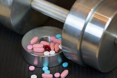 钢哑铃和五颜六色的维生素药片在健身房席子 库存图片