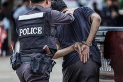 钢扣上手铐的警察,被拘捕的警察,专业警察必须是非常强的,官员拘捕 图库摄影