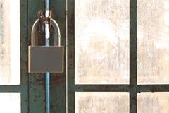 钢挂锁在老生锈的金属门 免版税库存图片