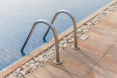 钢梯子和明白蓝色游泳池 库存图片