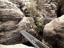钢梯子方式,在岩石之间的钢舷梯通过ferrata 在岩石固定的铁扭转的绳索 免版税库存照片