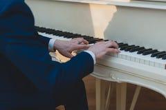 钢琴演奏家在一架白色钢琴使用 库存照片