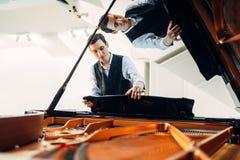 钢琴演奏家在表现前设置大平台钢琴 免版税库存照片