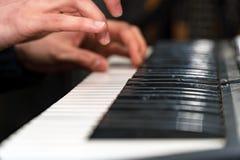 钢琴演奏家特写镜头的手 在合成器的戏剧 免版税库存图片