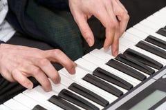 钢琴演奏家的手在合成器使用 免版税库存图片