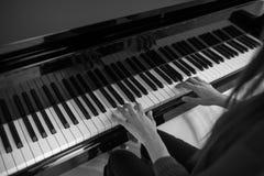 钢琴音乐钢琴演奏家现有量使用 乐器大平台钢琴细节用在白色背景的执行者手 免版税库存照片