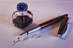 钢笔、蓝墨水和墨水池在白皮书板料 图库摄影