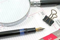 钢笔和放大镜在组织者 免版税库存照片
