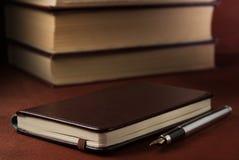 钢笔和笔记本在一张木桌上 图库摄影