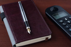 钢笔和笔记本在一张木桌上 免版税库存图片