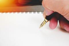 钢笔用holdingwriting署名概念的手空白的笔记本 免版税图库摄影
