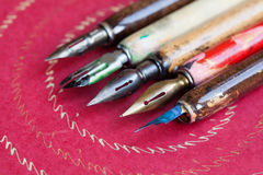 钢笔集合 书法手写辅助部件,葡萄酒五颜六色的艺术家笔,织地不很细桃红色纸背景 库存图片
