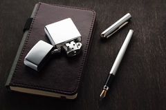 钢笔,一个老打火机,在一张黑暗的桌上的一个笔记本 免版税库存照片