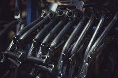 从钢管获得的金属制品在一个酒吧垂悬了在车间 摩托车的中央立场 免版税库存照片