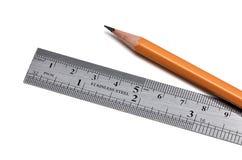钢统治者和木头铅笔 免版税库存照片