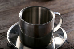 钢茶杯在木背景特写镜头 免版税图库摄影