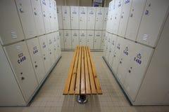 钢衣物柜行沿椅子,工作者的更衣室的在工作站点,在体育复合体保留个人属于 免版税库存图片