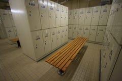 钢衣物柜行沿椅子,工作者的更衣室的在工作站点,在体育复合体保留个人属于 免版税库存照片