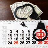 钢警察手铐、在日历o的美元金钱和4月15日 图库摄影