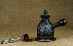 钢量匙用烤咖啡豆和做了黑黏土Ñ  offeepot在粗糙的帆布背景 库存图片