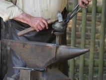 钢铁砧,在顶部说谎一个热的制件,铁匠过程的手一个制件在锤子的帮助下 免版税图库摄影