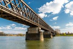 钢,一座铁路桥的晶格结构在一条河的有天空蔚蓝背景与白色云彩的在德国西部 免版税库存照片
