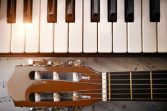 钢琴和调整的钉吉他和活页乐谱背景上面 免版税库存图片