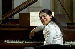 钢琴微笑的教师 免版税图库摄影