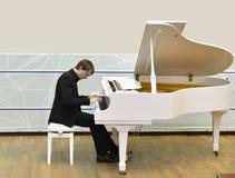 钢琴演奏家在白色大平台钢琴后排练 图库摄影