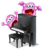钢琴的后面的两个桃红色妖怪 库存图片