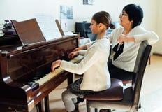 钢琴课在音乐学院、老师和学生 免版税库存图片