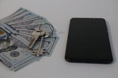 钥匙、金钱和手机 免版税库存图片