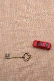 钥匙和一辆红色玩具汽车在帆布 库存照片