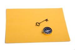 钥匙和指南针在纸片 免版税库存照片