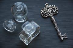 钥匙和香水在木背景 免版税图库摄影