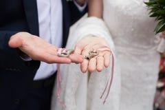 钥匙在新娘和新郎的手上 中断玻璃人传统婚礼 免版税库存照片