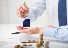 给钥匙的房地产开发商在桌的顾客 免版税库存图片