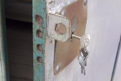 钥匙,忘记在金属门匙孔与强有力的顶上的锁的 免版税库存照片