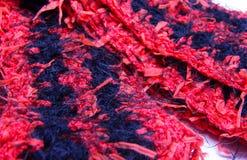钩编编织物有条纹图形的乐趣毛皮黑和红色围巾 库存照片