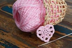 钩编编织物与丝球的华伦泰心脏在柳条busket 免版税库存图片