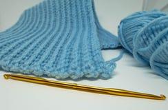 钩编编织物工作、钩针和蓝色毛线球 图库摄影