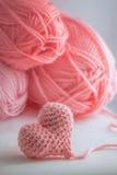 钩编编织物桃红色毛线心脏和丝球在软的温暖的光的 免版税库存图片