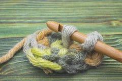 钩针编织链子特写镜头照片  土气钩针编织螺纹和一个竹勾子 温暖编织的绿色冬天毛线球并且钩编编织物在t 免版税库存图片