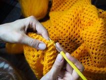钩针编织 妇女钩针编织在黑暗的背景的黄色毛线 手的特写镜头 免版税库存照片