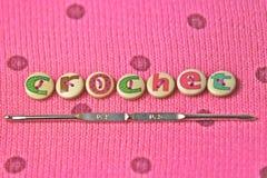 钩针编织在桃红色羊毛背景的有学问的按钮拼写了 免版税库存图片