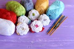 钩针编织花设置了,棉纱品丝球,另外大小勾子在紫色木背景的 五颜六色的钩针编织的玫瑰 免版税图库摄影