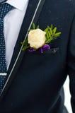 钮扣眼上插的花在新郎的夹克口袋上升了 图库摄影