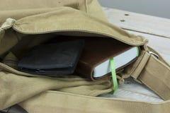 钱包和书在一个开放袋子 库存照片
