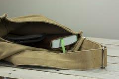 钱包和书在一个开放袋子 免版税库存照片