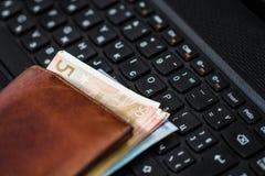 钱包和金钱在键盘 免版税库存图片